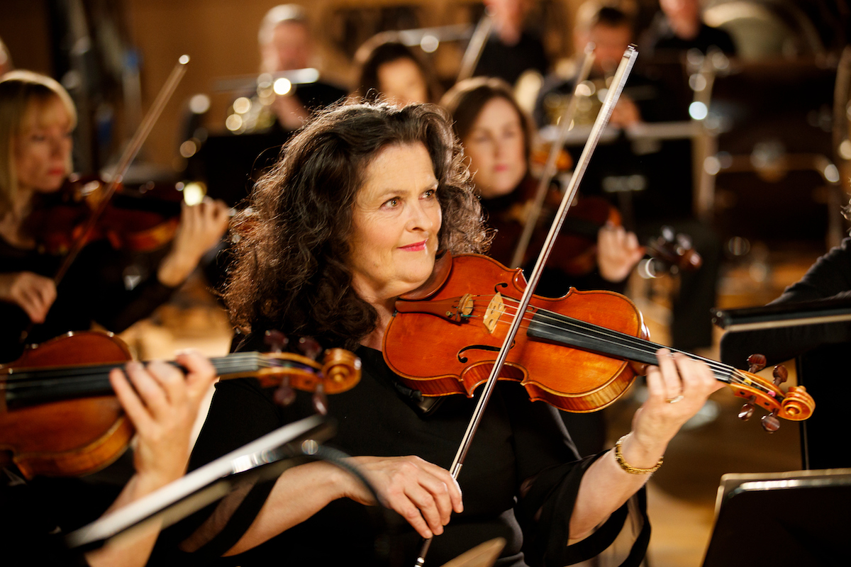 Woman playing violin and smiling