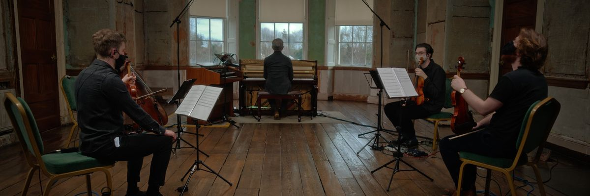 Brian Pepper sitting at a piano with a string quartet around him